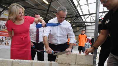 Bill Shorten's wife Chloe moves his tie as he lays a brick during a visit to a TAFE Campus in Perth.