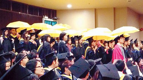 Several other students in the crowd joined in the protest by opening their own yellow umbrellas. (Supplied)