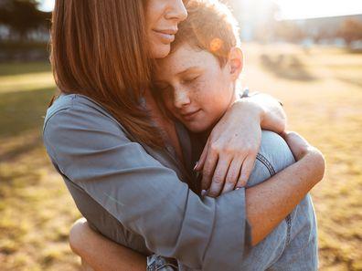 Woman embracing teenage son