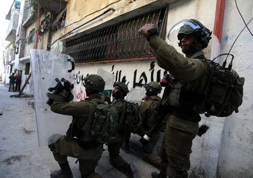 Israeli soldiers take position at Aroub refugee camp, north of the West Bank city of Hebron