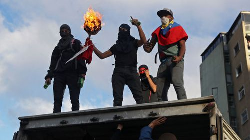 Protesters vandalise a lorry as thousands take to the streets during a demonstration against President Maduro in Caracas.