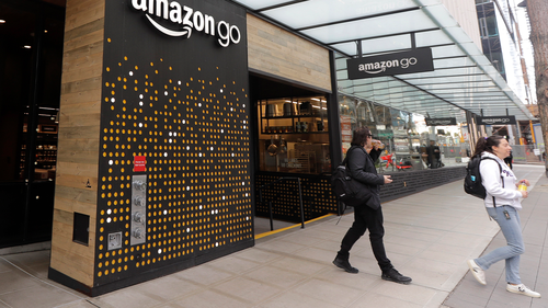 People walk out of an Amazon Go store, Wednesday, March 4, 2020, in Seattle. (AP Photo/Ted S. Warren)