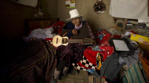 """In this Aug. 23, 2018 photo, 117-year-old Julia Flores Colque holds a """"charango,"""" a small Andean stringed instrument"""