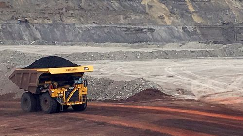 A dump truck hauls coal at an unspecified mine.
