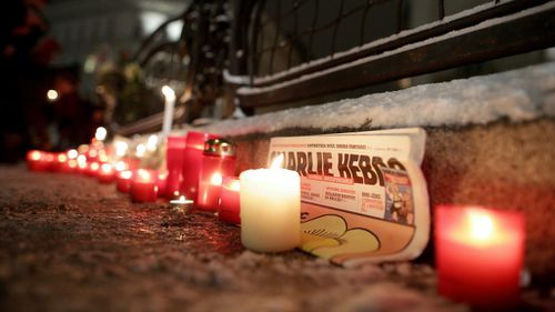 A copy of Charlie Hebdo surrounded by candles at a memorial in Vienna, Austria. (AAP)