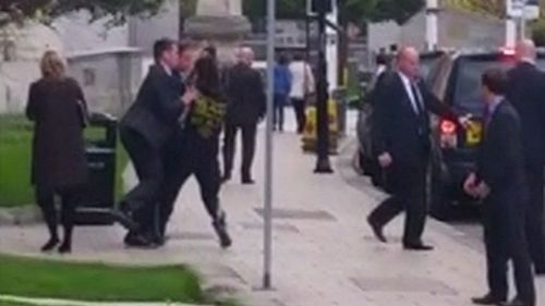 Mr Cameron's security team grab the man as he runs towards the PM. (BBC)