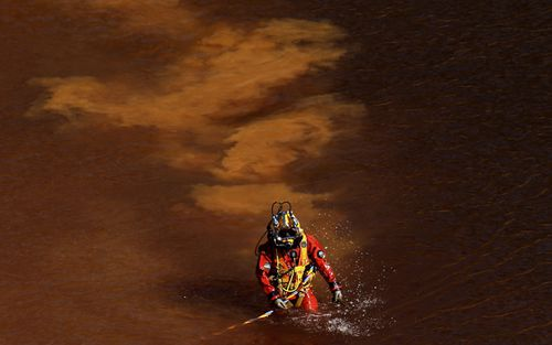 A diver walks out from a toxic man-made lake after a dive search for a third victim near the village of Mitsero outside of the capital Nicosia, Cyprus. Army captain Nicholas Metaxas was sentenced to seven life terms after he pleaded guilty to the premeditated murder and kidnapping of seven foreign women and girls.