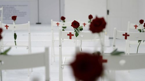 Twenty-six chairs were set up with roses in memory of each person killed in the shooting. (AAP)