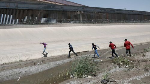 Migrants rush across the border between Juarez, Mexico, and El Paso, USA.