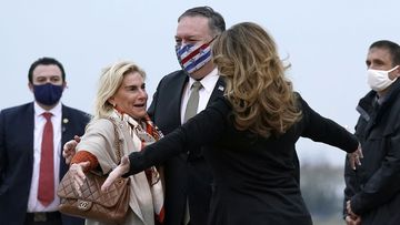 U.S. Secretary of State Mike Pompeo, center, and his wife Susan, right, embrace U.S. Ambassador to France Jamie McCourt, left, after stepping off a plane at Paris Le Bourget Airport, Saturday, Nov. 14, 2020, in Le Bourget, France.