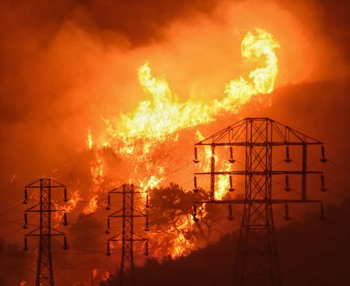 Flames burn near power lines in Sycamore Canyon near West Mountain Drive in Montecito. (AAP)