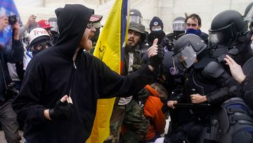 Violent protesters confront Capitol Police outside the Congress building.