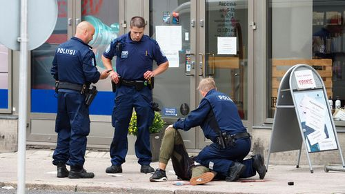 Police officers stand next to a person lying on the pavement in the Finnish city of Turku where several people were stabbed on August 18, 2017. (AFP)