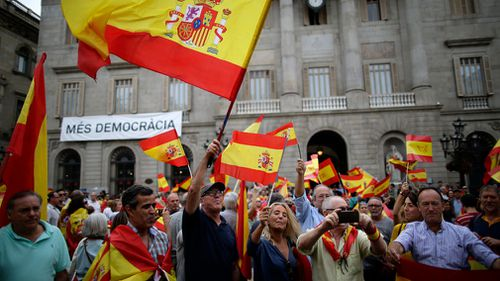 People wave Spanish flags while demonstrating against Catalonia's planned referendum on secession in Barcelona. (AP)
