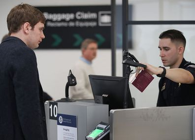 MIAMI, FL - FEBRUARY 27: A US Customs and Border Protection officer instructs an international traveller to look into a camera as he uses facial recognition technology at Miami International Airport in Miami, Florida.