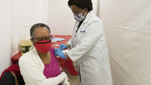 Dr, Jacqueline Delmont, Chief Medical Officer at Somos, gives Helen Washington, 76, the first dose of the coronavirus vaccine in the Bronx borough of New York.