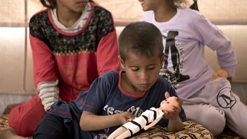 Dawoud Suleiman plays with a doll as his sisters Dawlat, left, and Omaima, sit with him in their tent at Dakuk Camp, near Kirkuk, Iraq. Traumatized by a series of tragedies suffered during three years of fighting in Iraq, the children live under an additional burden: Their father and other family members belonged to the Islamic State group.