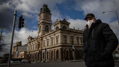 A man wearing a mask walks across Sturt Street in Ballarat on August 21, 2020 in Ballarat, Australia.
