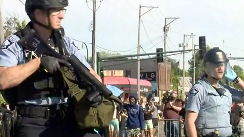 Armed police respond after a man was stabbed during riots in Minneapolis.