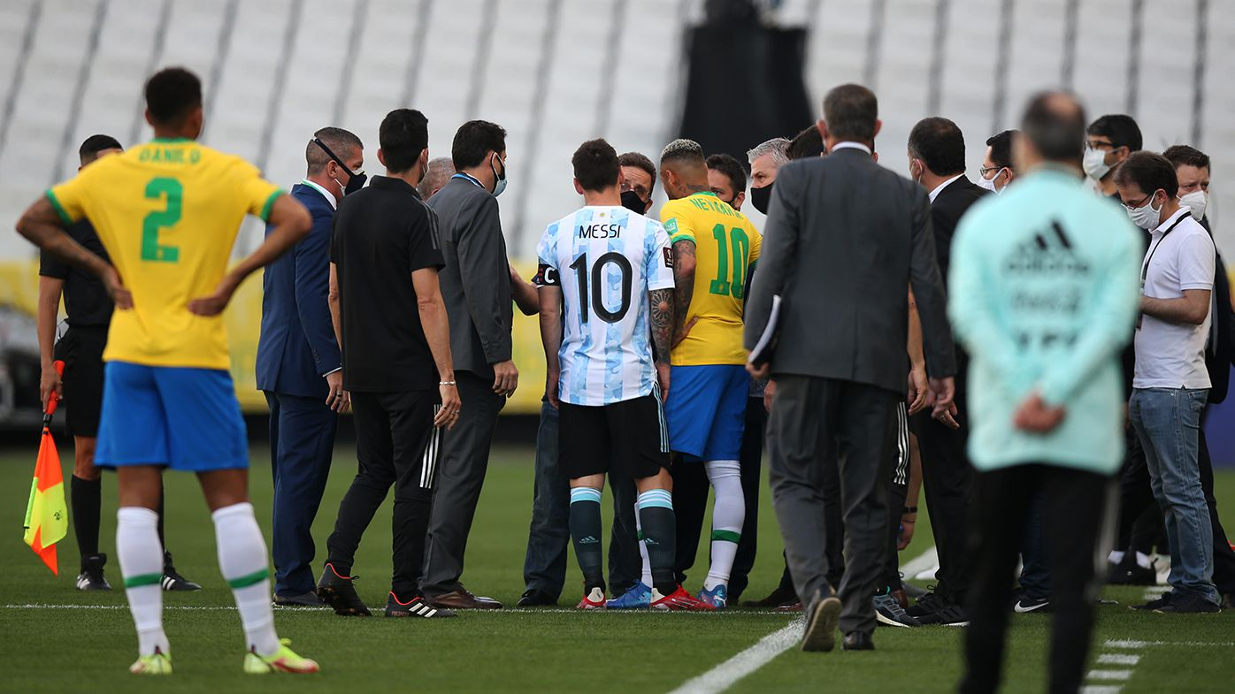 Lionel Messi of Argentina and Neymar Jr. of Brazil talk to health authorities as the match is delayed during a match between Brazil and Argentina.