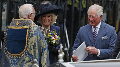 Prince Charles and Camilla, Duchess of Cornwall, laugh with a priest