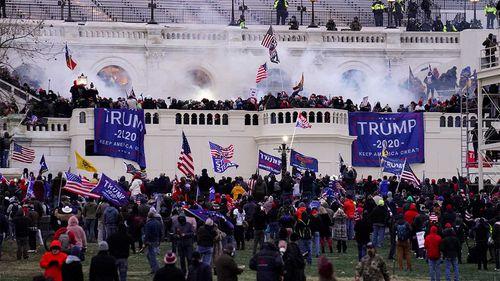 Protesters and rioters surrounding the US Capitol building.