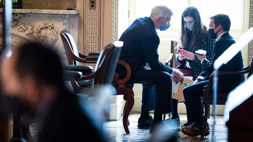 Bill Cassidy confers with staffers outside the chamber.
