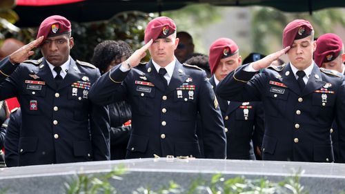 Members of the 3rd Special Forces Group Airborne 2nd Battalion leave pins and salute the casket after the burial of Army Sgt. La David Johnson. (AP)