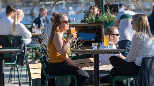 People gather for a drink at an outdoor bar in Stockholm, Sweden.