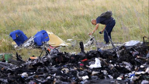 A Malaysian expert checks debris at the main crash site of flight MH17, which crashed flying over the eastern Ukraine region, near Grabovo, some 100 km east from Donetsk. Picture: AAP