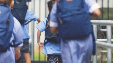 School children running into class