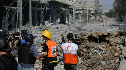 Non-governmental aid workers and media examine the devastation in Gaza. (AAP)