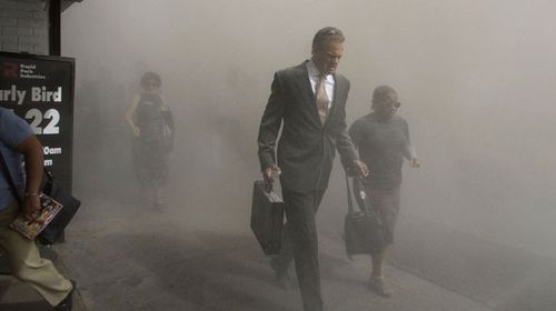 Pedestrians flee the dust-filled area surrounding the World Trade Center. (AAP)