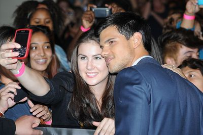 """Taylor Lautner takes a photo with a fan as he arrives at the world premiere of """"Abduction"""" in Hollywood."""