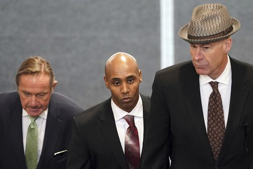 Noor, pictured with his legal team, shot Justine across his partner as she approached their squad car.