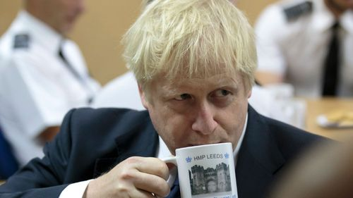 Britain's Prime Minister Boris Johnson takes a drink from a prison mug as he talks with prison staff during a visit to Leeds prison, Northern England, last week.