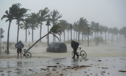 Two men walk their bicycle along a flooded street on the waterfront of Fort Lauderdale as Irma passes through. (AP)