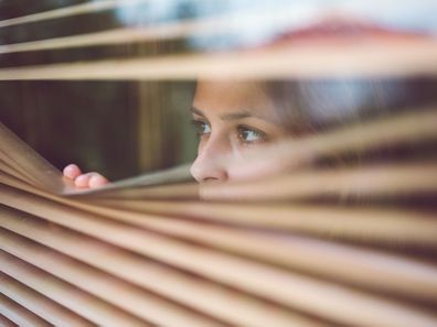 Woman looking through blinds in house