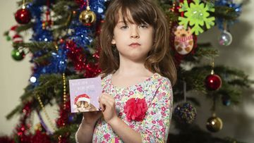 Florence Widdicombe, 6, poses with a Tesco Christmas card from the same pack as a card she found containing a message from a Chinese prisoner.