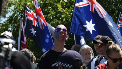 A member of the anti-Islam group Reclaim Australia appears with the French flag painted on his face. (AAP)