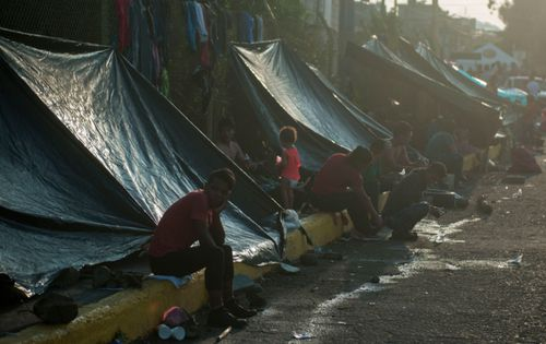 Honduran migrants start their day under improvised tents along a bridge that stretches over the Suchiate River, connecting Guatemala with Mexico.