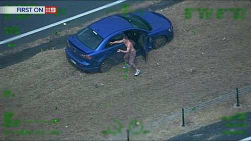 The man fires at police after the car he was driving hits road spikes. (9NEWS)