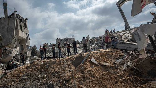 Men walk on the rubble of a residential building in Gaza City destroyed by an Israeli airstrike.