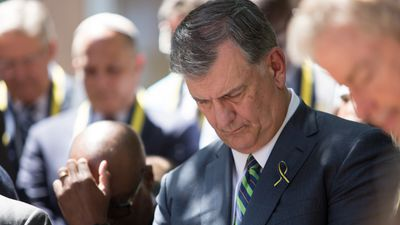 Dallas mayor Mike Rawlings bows his head in prayer.