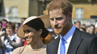 Meghan Markle, the Duchess of Sussex walks with her husband, Prince Harry as they attend a garden party at Buckingham Palace in London, Tuesday May 22, 2018. The event is part of the celebrations to mark the 70th birthday of Prince Charles.