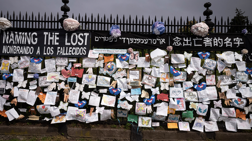 FILE - In this Thursday, May 28, 2020 file photo, a fence outside Brooklyn's Green-Wood Cemetery is adorned with tributes to victims of COVID-19 in New York.