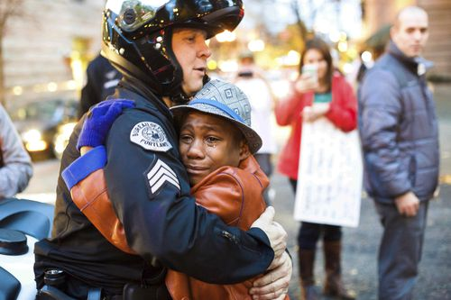 A Portland officer saw his sign and asked if he could have a hug, and an emotional Devonte embraced him in a picture that was widely shared. (AAP)