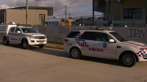 Police believe strong winds may have played a role in the collapse of the wall that left a worker with serious injuries to his head.