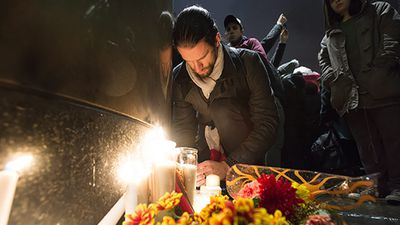 A man lights a candle at a vigil outside the French consulate in Montreal.