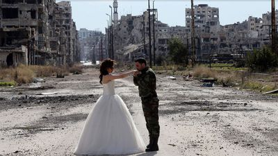 <p>Agence France-Presse photographer, Joseph Eid, accompanied the newlyweds and Mr Meray on their photo shoot, which saw the couple embrace in the eerily empty streets and pose inside heavily damaged buildings. </p><p>(Joseph Eid/AFP/Getty)</p>